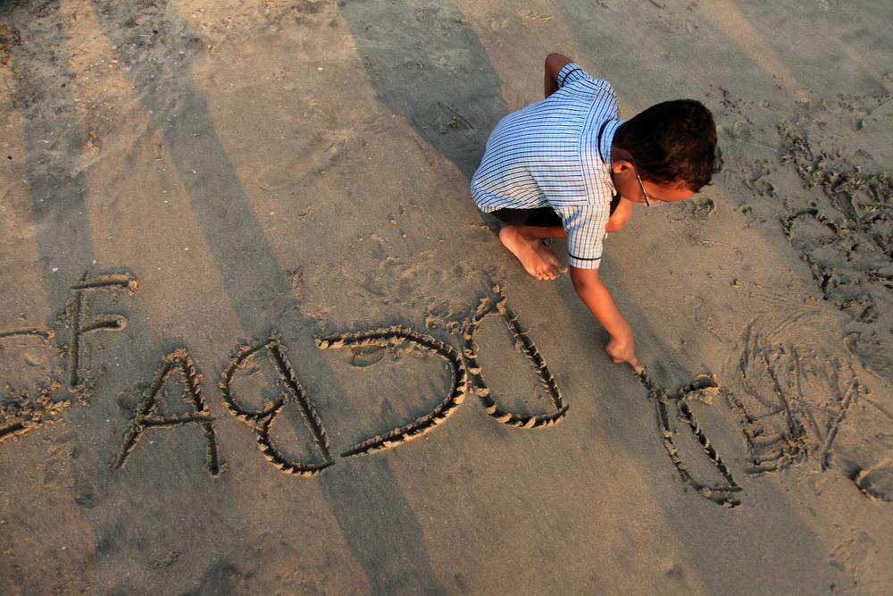 a boy is writing on the beach