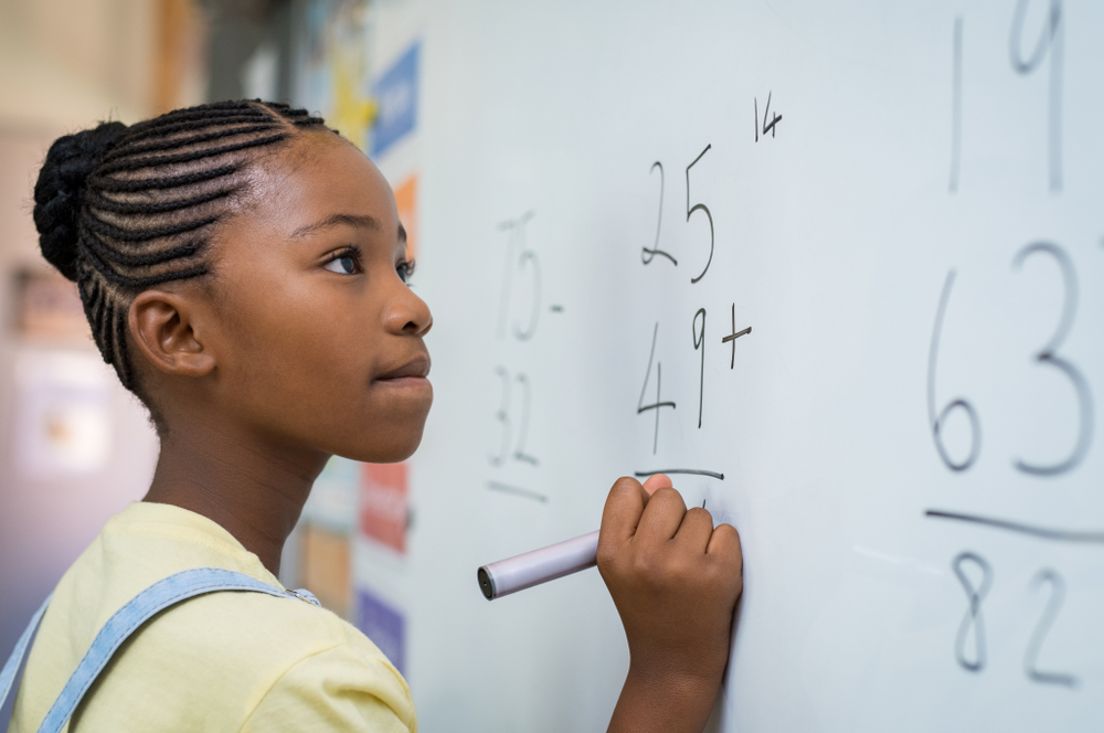 girl at math class writing on board