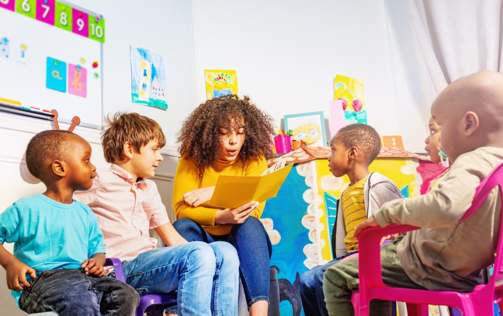 a teacher reading a book for kids