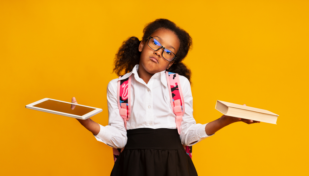 a girl with ipad and a book