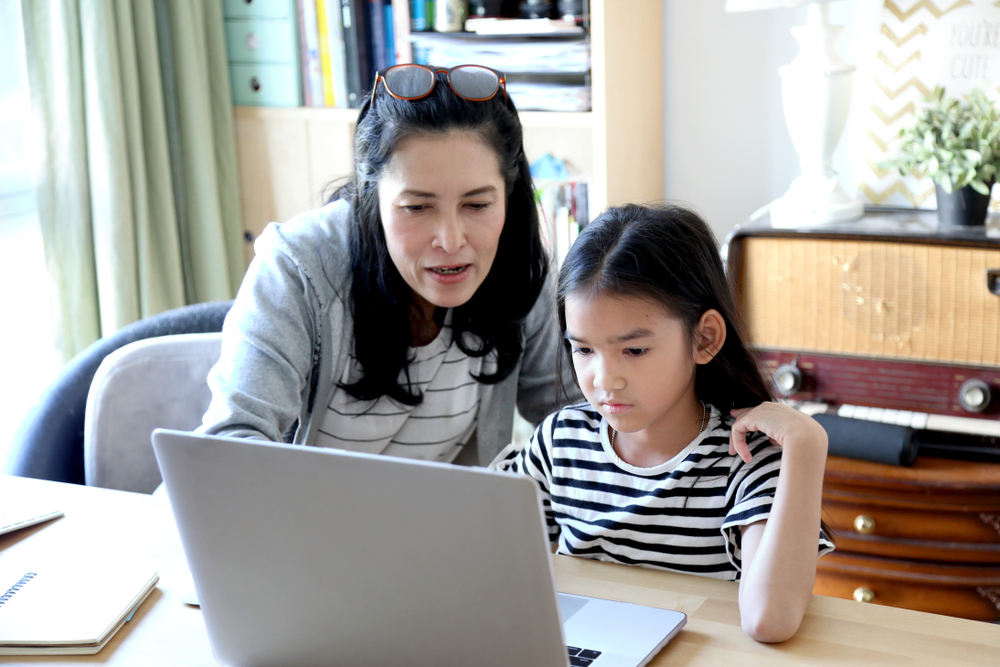 a teacher and a girl in front of a laptop
