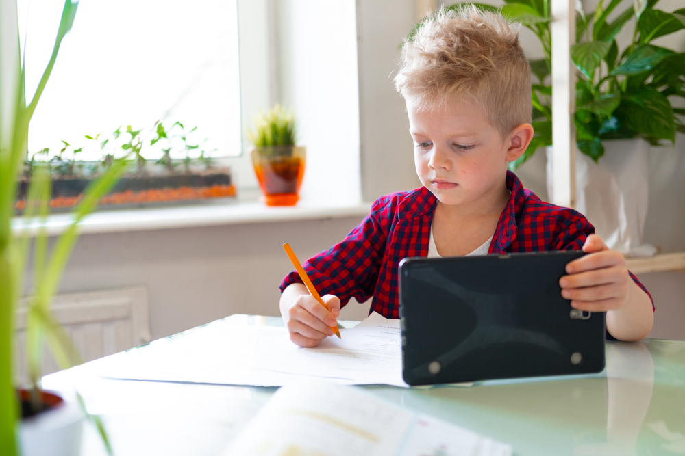 a boy is writing on a paper
