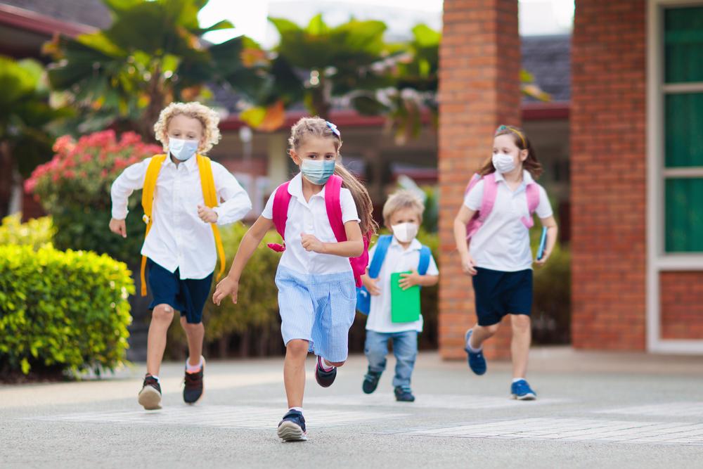 children running to school in masks