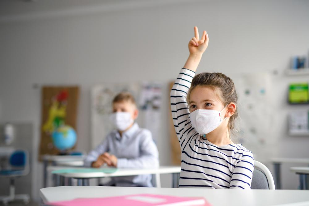 kid raising a hand at classroom