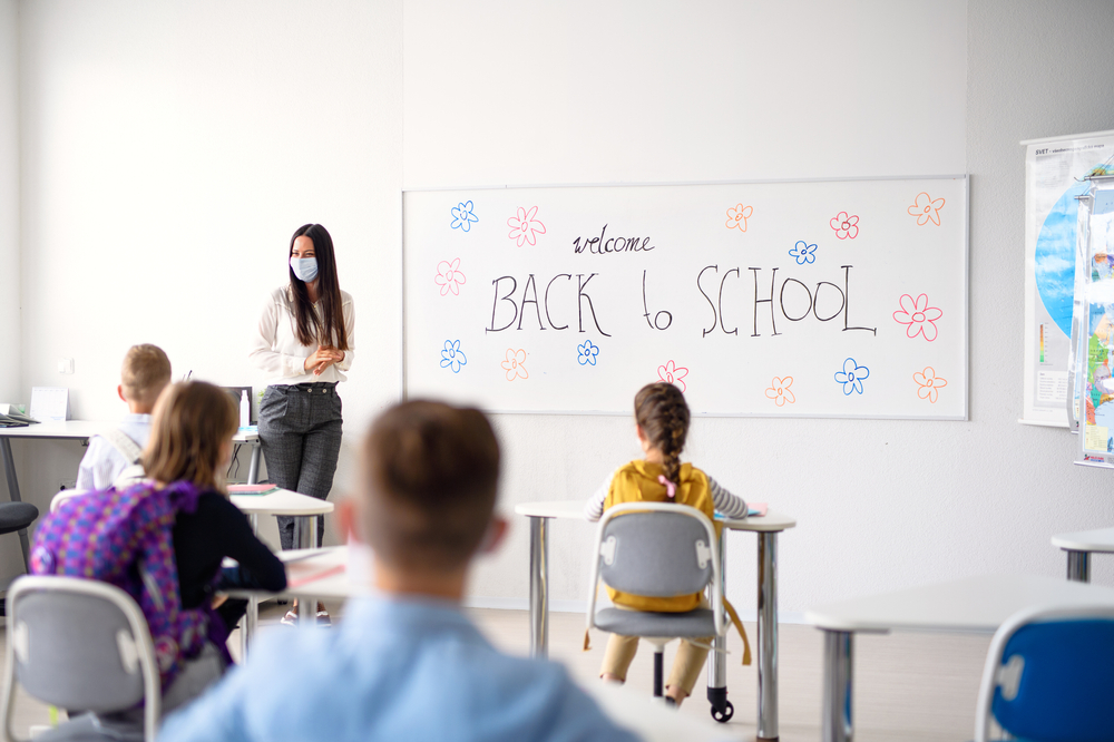 classromm and a teacher in mask